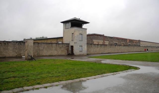 Muren som givetvis omger hela koncentrationslägret med ett av vakttornen. Bakom muren skymtar tegelfabriken