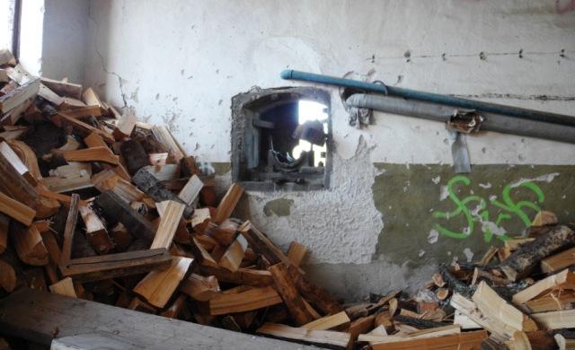Ved i massor. Hålet i väggen har sannolikt härbärgat kraftöverföringen till maskinen